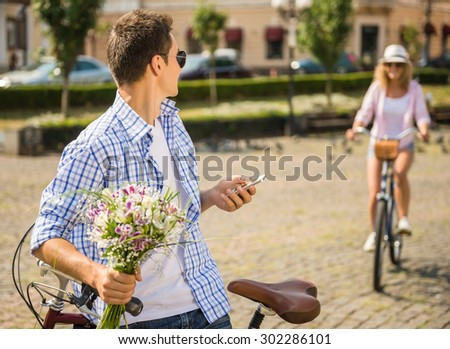 Young man in sunglasses with bicycle holding flowers and meeting his girlfriend at the city street. - stock photo