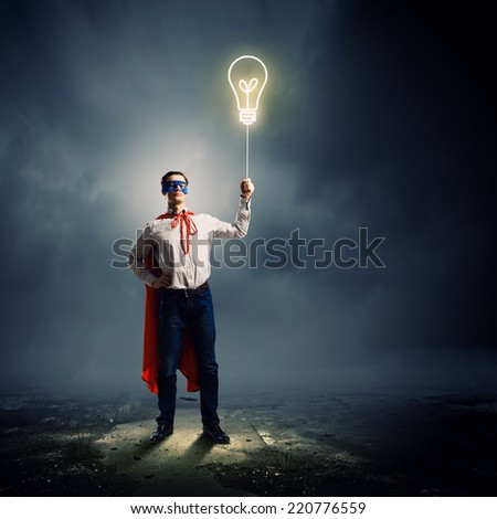 Young man in superhero costume holding balloon in hand