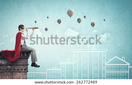 Young man in superhero costume on top of building - stock photo