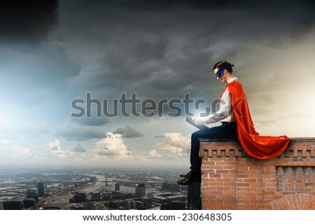 Young man in superhero costume reading book - stock photo