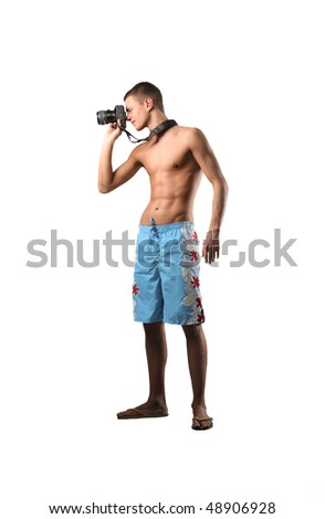 Young man in swimsuit using a camera - stock photo