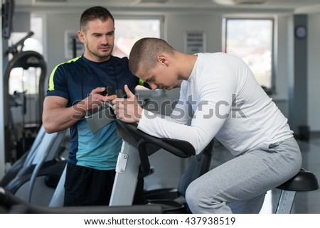 Young Man In The Gym with Personal Trainer - Exercising His Legs Doing Cardio Training On Bicycle - stock photo