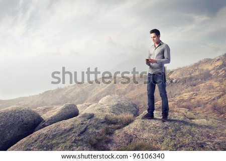 Young man in the mountains using a mobile phone - stock photo