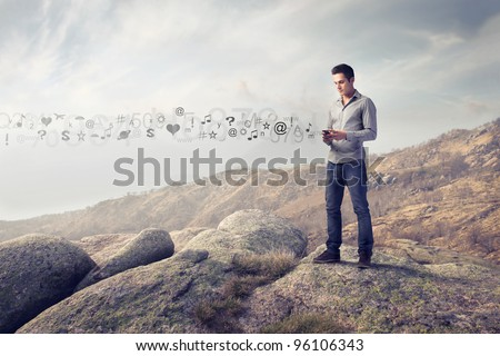 Young man in the mountains using a mobile phone and symbols coming out from it - stock photo