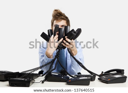 young man in the office and answering several phones at the same time - stock photo