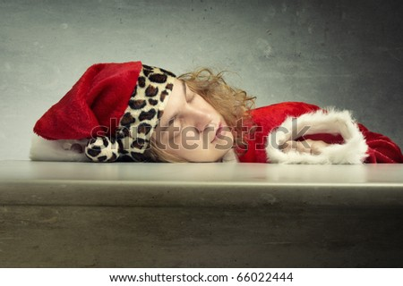 Young man in the red furry Santa Claus costume sleeping on the table in the grungy room - stock photo