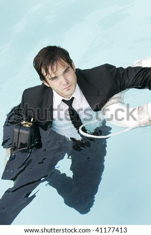 Young man in the water wearing a suit, holding onto his briefcase, and a life preserver. - stock photo