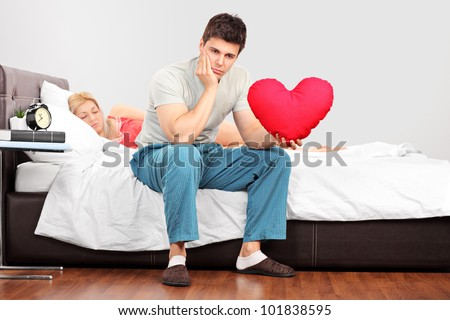 Young man in thoughts holding a heart shaped pillow while his girlfriend fall asleep - stock photo