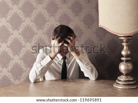 Young man in tie puts his hands in his hair - stock photo