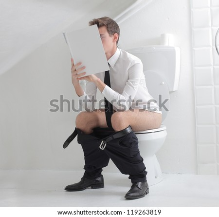 Young man in tie reading a magazine on a toiler - stock photo