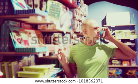 Young man in toy store calls by telephone to the wife to consult