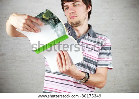 young man in trouble to decipher a book - stock photo