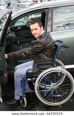 Young man in wheelchair getting in his car - stock photo