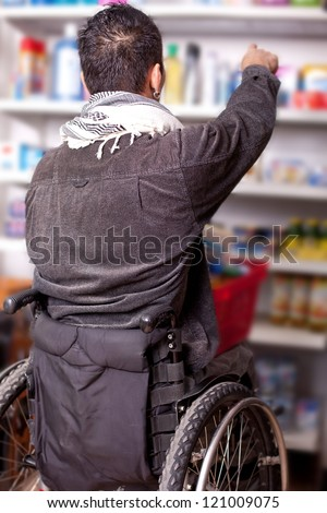 young man in wheelchair in Barrier-free supermarket is looking for some food in the shop, disabled young man is shopping