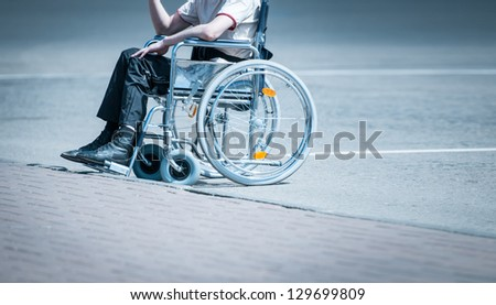 Young man in wheelchair on the road near pavement alone without face to be seen. Hard life of disabled people. Lonely and helpless person. - stock photo