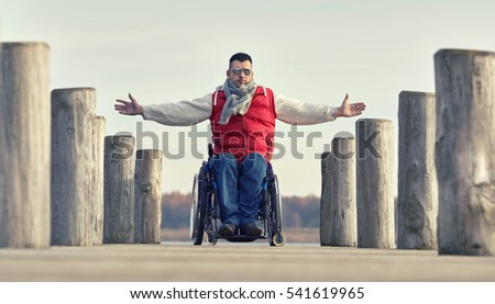 young man in wheelchair with wide opened arms enjoying his life at a lake in winter
