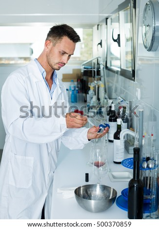 Young man in white coat checking wine acidity and sugar saturation in chemical laboratory on winery
