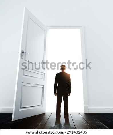 young man in white room with doors open - stock photo