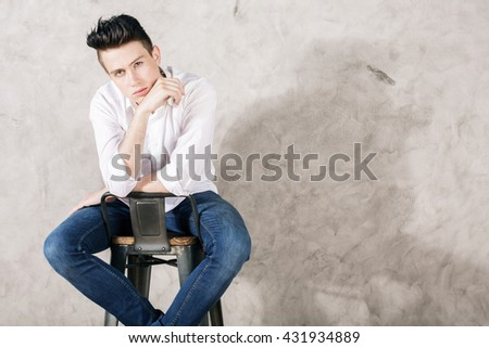 Young man in white shirt and jeans sitting backwards on chair against concrete wall - stock photo