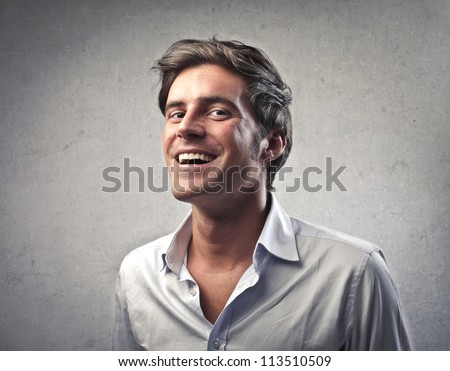 Young man in white shirt smiling - stock photo