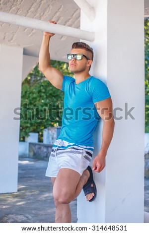 Young man in white shorts and blue shirt posing.