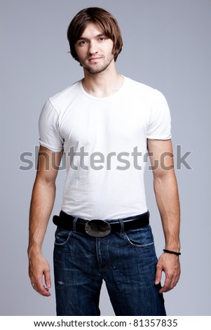 young man in white t-shirt and jeans, studio shot - stock photo