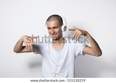 young man in white t-shirt is dancing and listening to music on headphones - stock photo