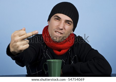 Young man in winter clothes being very upset and showing obscene gesture - stock photo