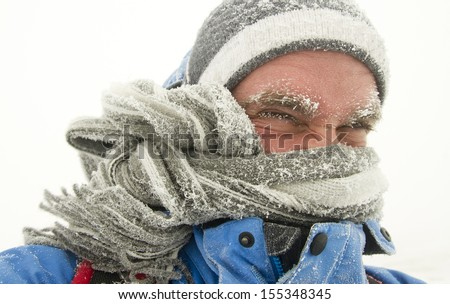 young man in winter storm with frozen eyebrows - stock photo