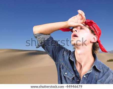 Young man in with eyes closed wearing red bandana wiping forehead. Horizontal shot. - stock photo