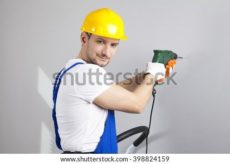 Young man in yellow protective helmet with electric drill making hole in wall