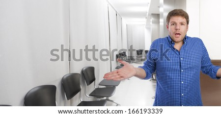 young man indifference gesture in office or waiting room - stock photo