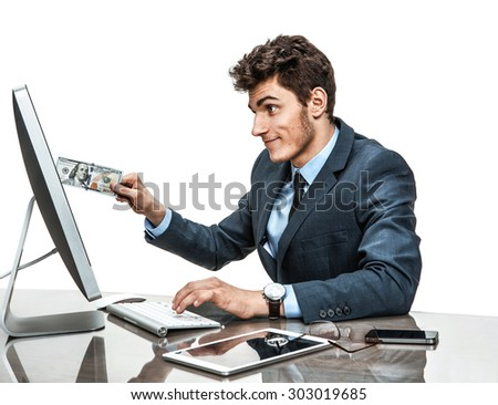 Young man inserting a dollar into a monitor, paying online concept / modern businessman at the workplace working with computer - stock photo