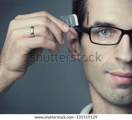 Young man inserting a SD Card into his head - stock photo