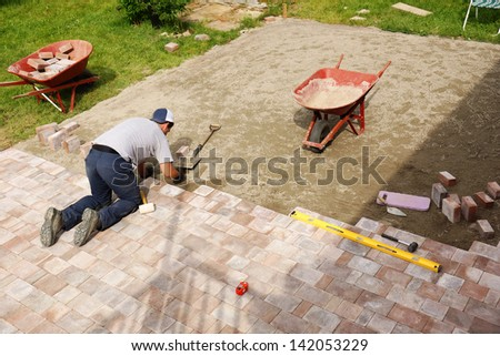 Young man installing paver bricks for large patio, paving backyard - stock photo