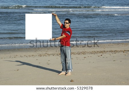 young man insurance a white poster in the beach, where it can write its message ... - stock photo