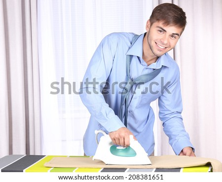 Young man ironing clothes in room - stock photo