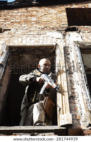 Young man is aiming from the window - stock photo