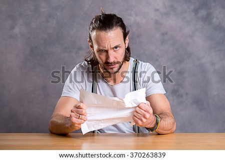 young man is annoyed about a letter - stock photo