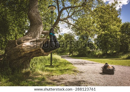 Young man is being eaten by a big tree. His travel belongings are situated next to the tree. A path and the greenery are visible in the background. - stock photo