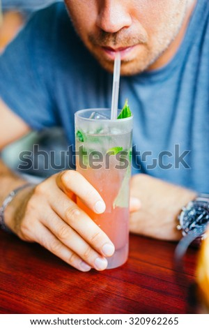 Young man is drinking cocktail outdoors