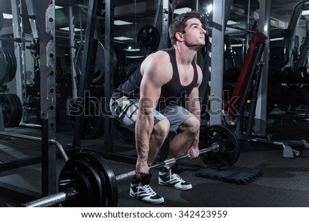 young man is engaged in bodybuilding at the gym - stock photo