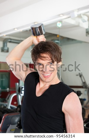 Young man is exercising with barbell in gym to strengthen the muscles