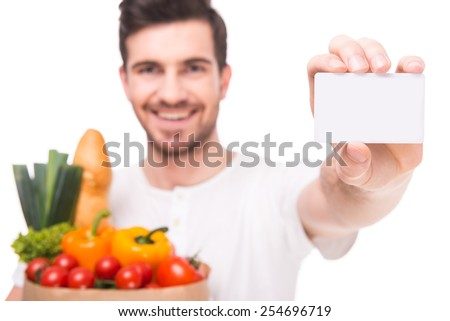 Young man is holding a bag full of vegetables and showing visit card, on white background. - stock photo