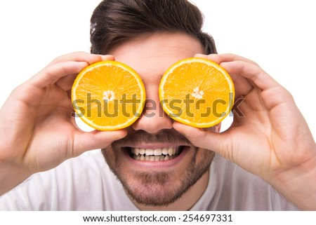 Young man is holding oranges in front of his eyes.