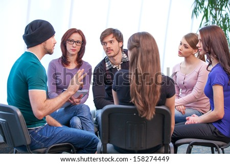 Young man is holding workshop. Discussing several issues and how to solve them - stock photo