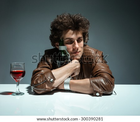 Young man is hugging a bottle of wine / photo of youth addicted to alcohol, alcoholism concept, social problem - stock photo
