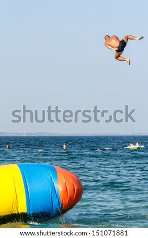 Young man is jumping with inflatable water catapult balloon on the sea shore - stock photo