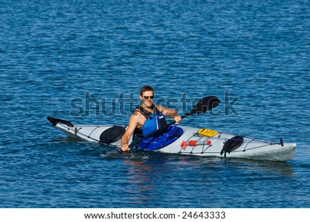 Young man is kayaking in calm blue waters of Mission Bay, San Diego, California. Copy space on top. - stock photo