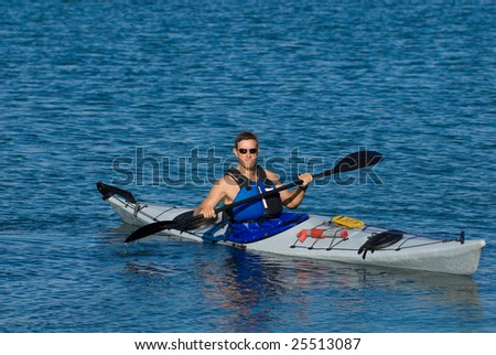 Young man is kayaking in calm blue waters of Mission Bay, San Diego, California looking at the viewer. Copy space on top.